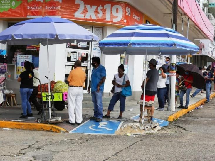 Comerciantes prestan sombrillas a cuenta habientes de bancos